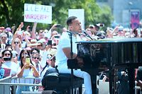 John Legend performs at the piano on stage during a 'Familes Belong Together' march and rally in Los Angeles, California on June 30, 2018 where a thousands turned out to decry the Trump administration's detention of families policy at the US Mexico border.  Thousands of demonstrators, baking in the heat and opposed to the US immigration policy, marched across the country Saturday, June 30, 2018 to protest the separation of families under President Donald Trump's hardline agenda.     / AFP PHOTO / Frederic J. BROWN