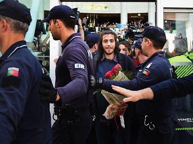 Winner of 2017 Eurovision contest Salvador Sobral (2ndR), escorted by policemen, smiles upon his arrival at Humberto Delgado Lisbon's airport on May 14, 2017.   / AFP PHOTO / PATRICIA DE MELO MOREIRA