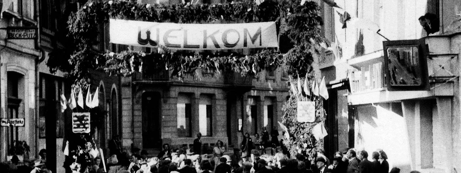 In der Groussstrooss wurden die amerikanischen Soldaten mit einer Ehrenpforte von den Ettelbrücker Bürgern empfangen. Diese war mit zahlreichen luxemburgischen Fahnen dekoriert.