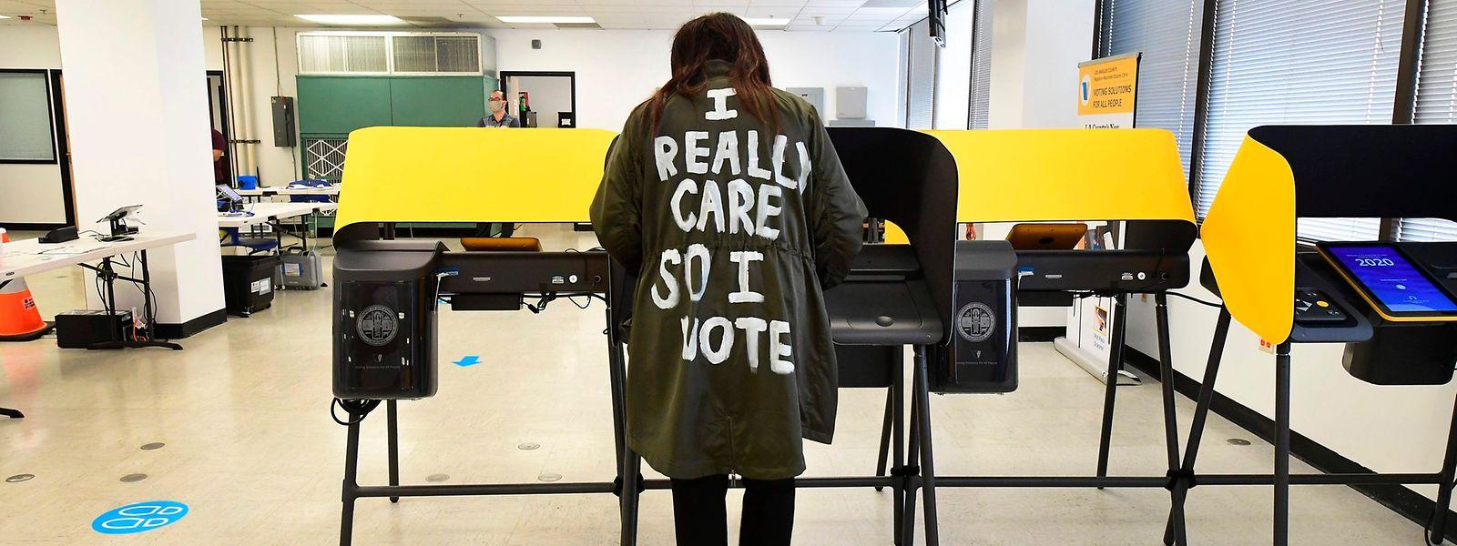"""Eine Frau mit der Aufschrift """"Ich sorge mich, deswegen wähle ich"""" auf dem Rücken ihres Mantels gibt ihre Stimme ab."""