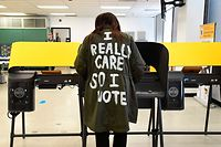 """TOPSHOT - Wearing a coat reading """"I Really Care So I Vote"""" written on the back, Tonya Swain votes in the 2020 US elections at the Los Angeles County Registrar in Norwalk, California on October 19, 2020. - The coat is a reference to one worn by US First Lady Melania Trump which read """"I Really Don't Care Do You?"""". Voter turnout is ten times higher than in 2016 in California according the Secretary of State Alex Padilla as over 600,000 Los Angeles County ballots are already at the county registrar. (Photo by Frederic J. BROWN / AFP)"""