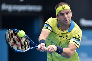 Gilles Muller of Luxembourg hits a return to Grigor Dimitrov of Bulgaria in their men's semi-final match at the Sydney International tennis tournament in Sydney on January 15, 2016. AFP PHOTO / Peter PARKS -- IMAGE RESTRICTED TO EDITORIAL USE -  NO COMMERCIAL USE