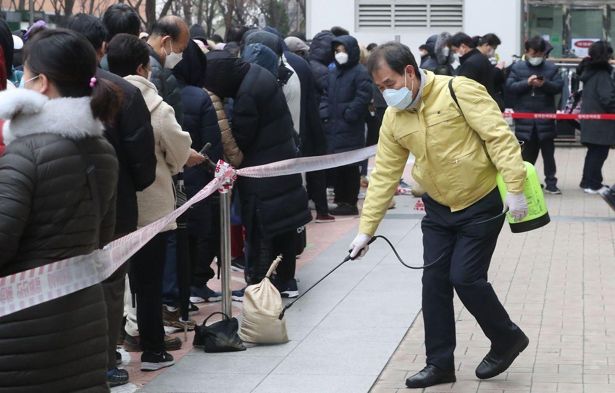 Un homme pulvérise du désinfectant alors que les gens font la queue pour acheter des masques dans un grand magasin de Séoul.