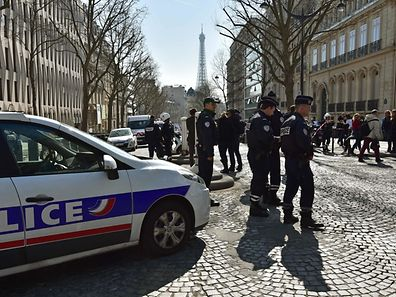 French Police officers stand guard outside the main entrance  of the Paris offices of the International Monetary Fund