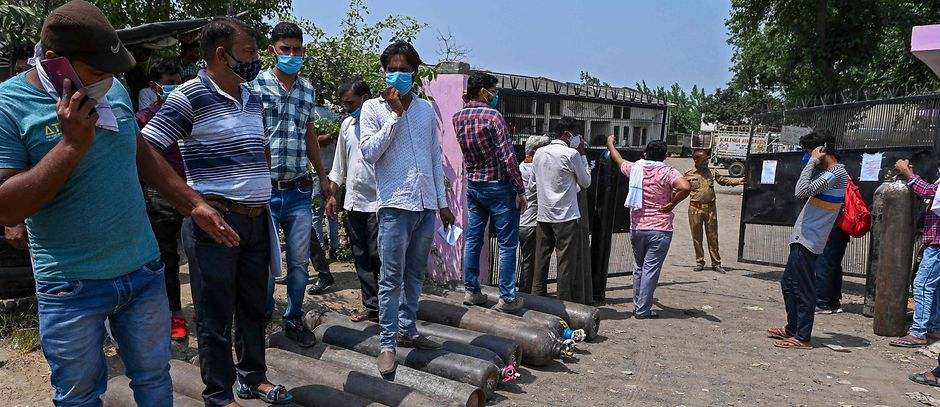 People wait to refill their cylinders with medical oxygen for the Covid-19 coronavirus patients at Kalinga oxygen refilling centre in Moradabad on May 5.