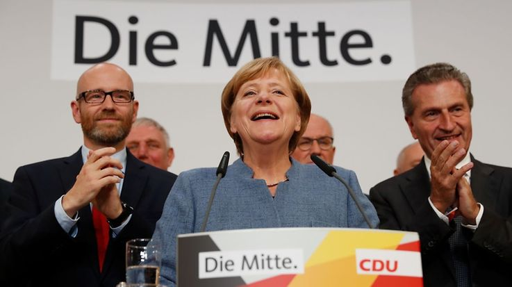 German Chancellor and CDU party leader Angela Merkel (C) addresses supporters after exit poll results were broadcasted on public television at an election night event at the party's headquarters in Berlin during the general election on September 24, 2017. Germany voted in a general election expected to hand Chancellor Angela Merkel a fourth term, while the hard-right Alternative for Germany (AfD) party is predicted to win its first seats in the national parliament. / AFP PHOTO / Odd ANDERSEN