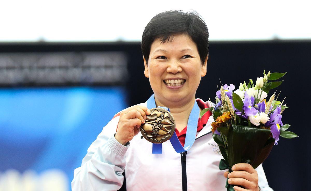Madame Ni pose fièrement avec sa médaille de bronze des Jeux européens à Minsk, synonyme de cinquième participation aux Jeux olympiques