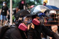 In this picture taken on August 25, 2019, Abby (L), 19, and her boyfriend Nick, 20, wait for tear gas to be fired by police as they attend a protest in Tsuen Wan, an area in the New Territories in Hong Kong. - A gas mask lovingly adjusted, a hand squeezed before approaching police lines�and a frantic search through swirls of tear gas -- Abby and Nick's relationship has blossomed on the barricades during Hong Kong's long summer of protest.� (Photo by Anthony WALLACE / AFP) / TO GO WITH AFP STORY HONG KONG-POLITICS-CHINA-UNREST-PROTEST,FOCUS BY AIDAN JONES AND JASMINE LEUNG