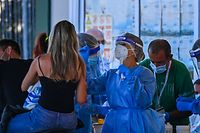 """Holidaymakers on a motorbike (L) returning from Sardinia by ferry undergo a compulsory drive-through swab test on August 23, 2020 at the port of Civitavecchia, northwest of Rome, during the COVID-19 infection, caused by the novel coronavirus. - Italy has recorded 1,071 new cases of coronavirus in the last 24 hours, breaking the symbolic barrier of 1,000 cases per day for the first time since May 12, according to an official report published on August 22, 2020. """"61% (of these new cases) are linked to holiday returns,"""" and more specifically 45% (97 cases) concern returns from the island of Sardinia, which had been spared by the first wave of the virus but where the comings and goings of careless tourists and revellers have contributed to the spread of the virus. (Photo by Vincenzo PINTO / AFP)"""