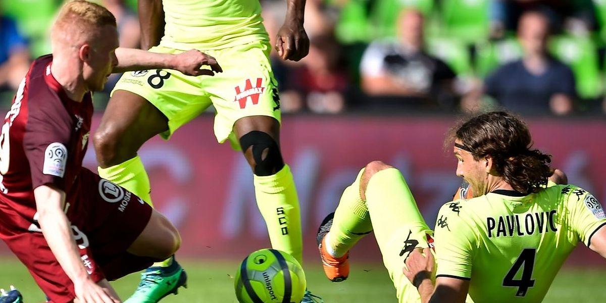 Florent Mollet à la lutte avec Mateo Pavlovic. Battu sur sa pelouse, le FC Metz est officiellement relégué en L2.