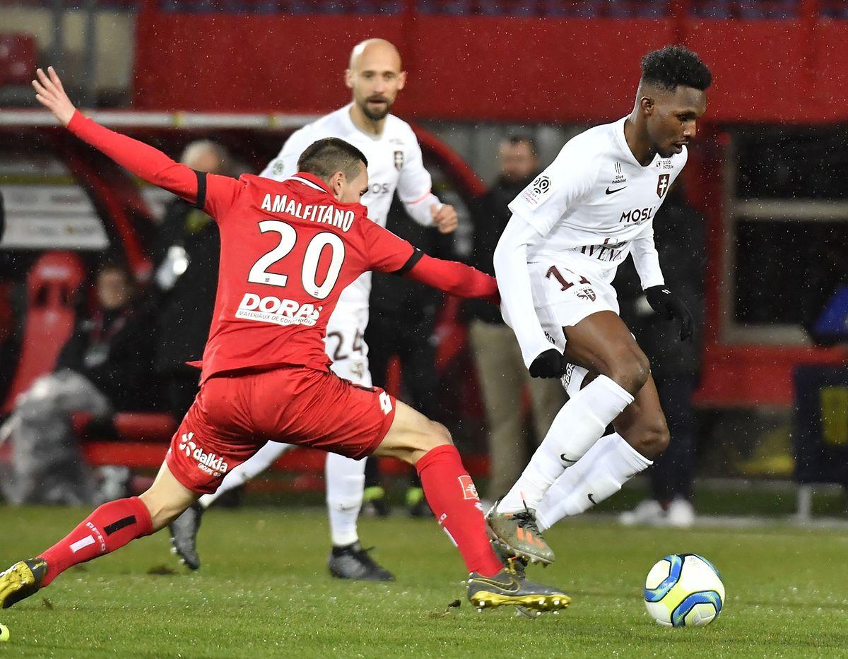 Opa Nguette (FC Metz, à dr.) évite le milieu de Dijon Romain Amalfitano (n°20, en rouge) sous le regard de Renaud Cohade