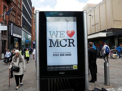 People walk past a sign in central Manchester