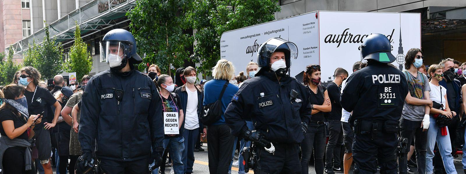 Teilnehmer einer Gegendemonstration einer Kundgebung gegen die Corona-Maßnahmen stehen der Polizei gegenüber.
