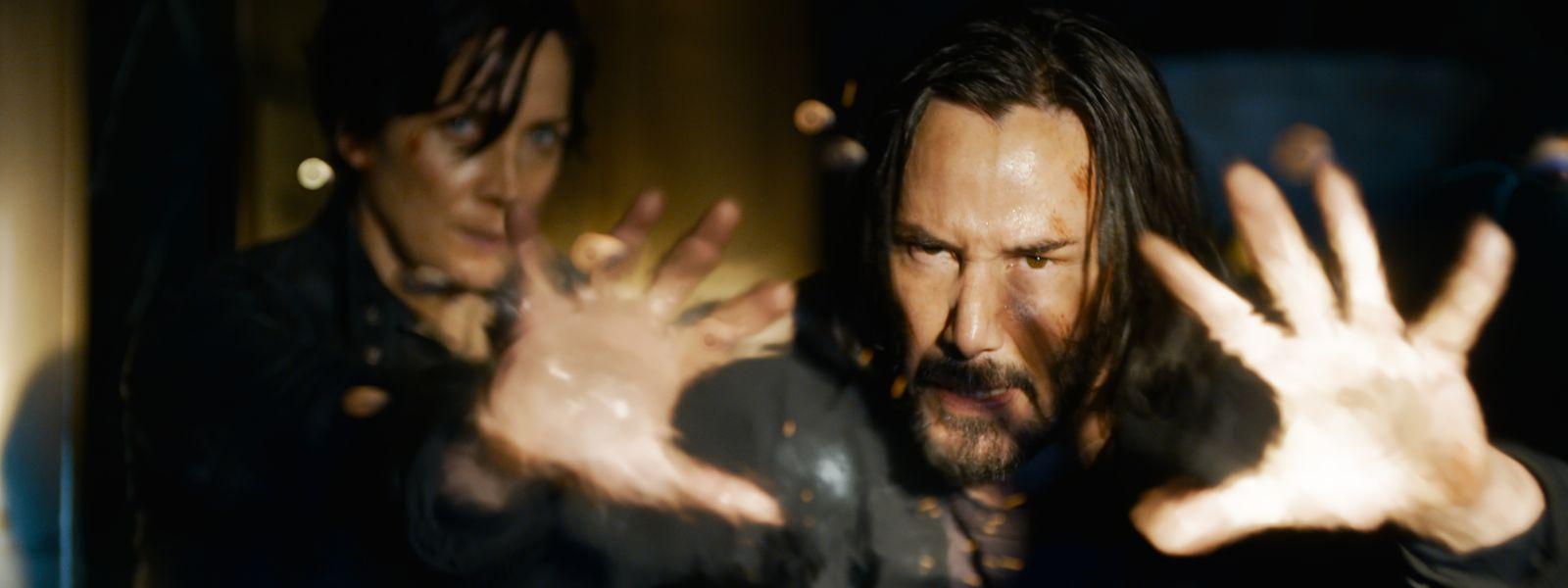 """Carrie-Anne Moss als Trinity und Keanu Reeves als Neo in einer Szene des Films """"Matrix 4 - Resurrections""""."""