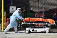 (FILES) In this file photo taken on April 02, 2020 Medical staff move bodies from the Wyckoff Heights Medical Center to a refrigerated truck on April 2, 2020 in Brooklyn, New York. - New York state's death toll rose to 3,565 on April 4, 2020, Governor Andrew Cuomo said, up from 2,935 the previous day, in the largest 24-hour jump recorded there. The state has now recorded 113,704 positive cases -- 63,306 in New York City -- just 6,000 short of hard-hit Italy's total. (Photo by Angela Weiss / AFP)