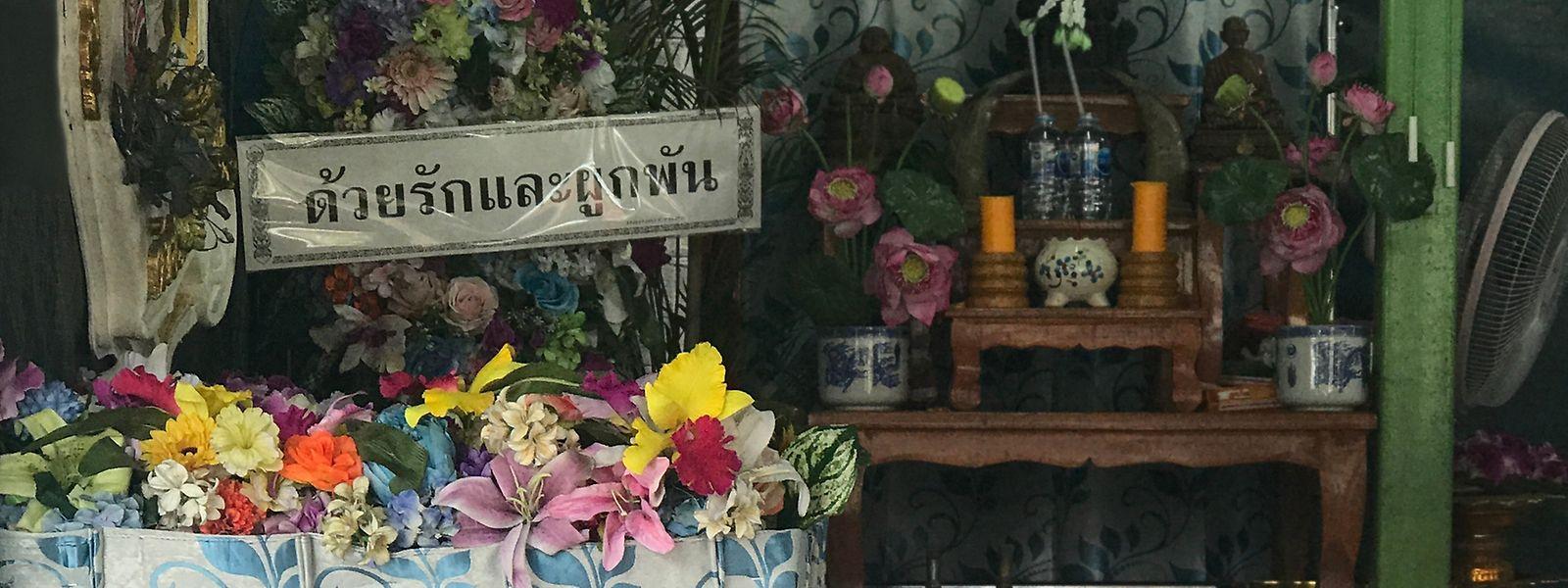 Blumen, Kerzen und Räucherstäbchen setzen den Rahmen für das letzte Geleit.