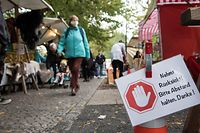 """A sign reading """"Please keep your distance. Thank you."""" is seen at the weekly market in Berlin Kreuzberg on October 20, 2020 in Berlin. - The Berlin Senate has tightened the corona requirements in view of the rising number of infections. The state government decided to make masks compulsory for markets and ten busy streets in the capital, as the Senate announced after the session. It also made the """"urgent recommendation"""" to wear a mask in public places where the minimum distance of 1.5 metres cannot be maintained. (Photo by STEFANIE LOOS / AFP)"""