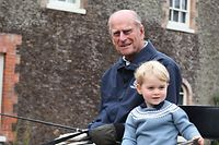 """A handout picture released by Kensington Palace and Britain's Duke and Duchess of Cambridge on April 12, 2021 and taken by the Duchess shows Britain's Prince Philip, Duke of Edinburgh (L) and Britain's Prince George of Cambridge (R) sat in a horse carriage at Anmer Hall in the village of Anmer in Norfolk, eastern England, on an unspecified date in 2015. (Photo by THE DUCHESS OF CAMBRIDGE / KENSINGTON PALACE / AFP) / RESTRICTED TO EDITORIAL USE - MANDATORY CREDIT  """" AFP / KENSINGTON PALACE / THE DUCHESS OF CAMBRIDGE """"  -  NO MARKETING NO ADVERTISING CAMPAIGNS - NO USE IN SOUVENIRS OR MEMORABILIA - NO SALES - RESTRICTED TO SUBSCRIPTION USE - NO CROPPING OR MODIFICATION - FOR USE UNTIL DECEMBER 31, 2021 - DISTRIBUTED AS A SERVICE TO CLIENTS /"""