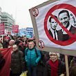 Protesters hold up a sign with the crossed-out Austrian Chancellor Sebastian Kurz (L)(OeVP) and Heinz - Christian Strache (Freedom Party Austria, FPOe) during a demonstration against the current Austrian government and for Human Asylum Policy in Vienna, on January 13, 2018. / AFP PHOTO / ALEX HALADA