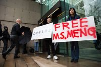Robert Long (L) and Ada Yu hold signs in favor of Huawei Technologies Chief Financial Officer Meng Wanzhou outside her bail hearing at British Columbia Superior Courts following her December 1 arrest in Canada for extradition to the US, in Vancouver, British Columbia on December 11, 2018. (Photo by Jason Redmond / AFP)