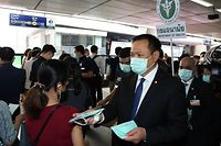 "This handout photo taken and released on February 7, 2020 by Thailand's Public Health Ministry shows Health Minister Anutin Charnvirakul (R) handing out protective facemasks to members of the public at a BTS Skytrain station in Bangkok. - Thailand's health minister lashed out at 'western' tourists on February 7 for not wearing face masks amid the coronavirus outbreak, suggesting they be kicked out of the country for putting others at risk. (Photo by Handout / Thailand Public Health Ministry / AFP) / RESTRICTED TO EDITORIAL USE - MANDATORY CREDIT ""AFP PHOTO / Thailand's Public Health Ministry"" - NO MARKETING - NO ADVERTISING CAMPAIGNS - DISTRIBUTED AS A SERVICE TO CLIENTS"