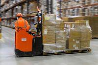 12.05.2021, Sachsen-Anhalt, Sülzetal: Ein Mitarbeiter des Amazon Logistikzentrums fährt mit Paketen an Hochregalen vorbei. Der Versand-Händler hatte den neuen Standort in Sachsen-Anhalt im August 2020 eröffnet. Foto: Klaus-Dietmar Gabbert/dpa-Zentralbild/dpa +++ dpa-Bildfunk +++