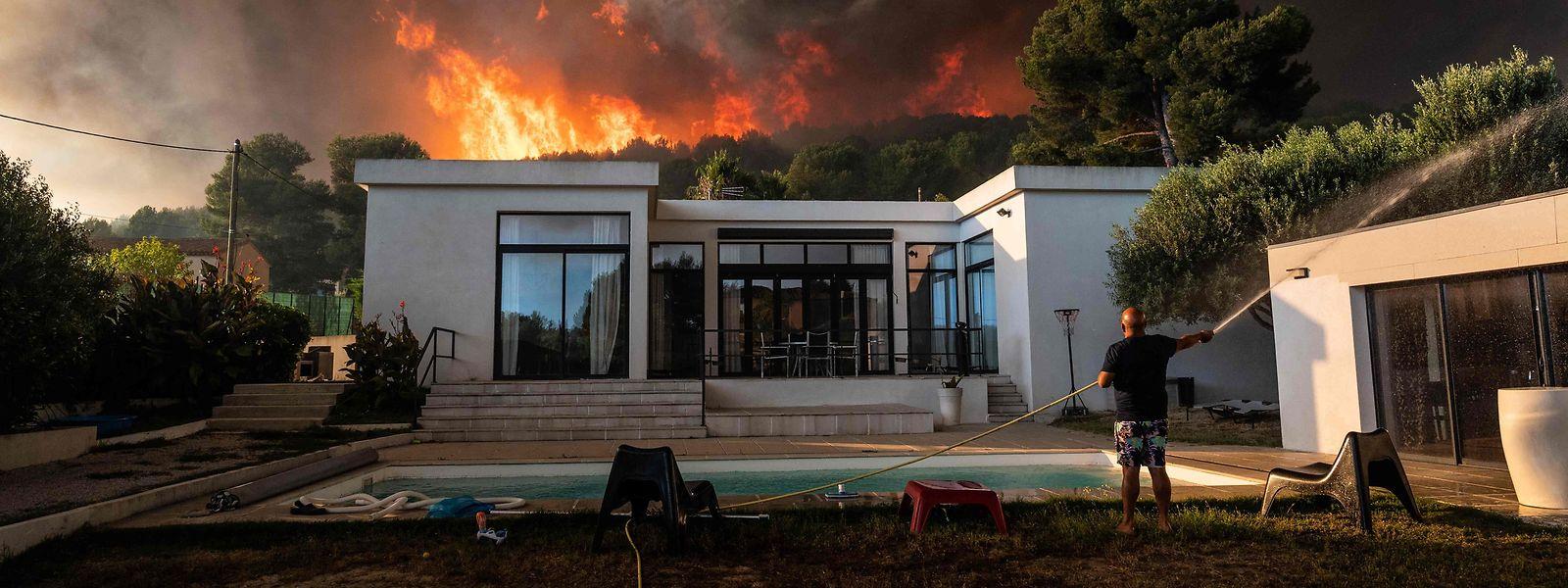 Ein Mann versucht mit einem Gartenschlauch, sein Haus vor der Hitze zu schützen.
