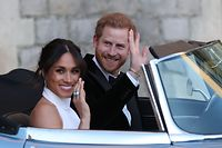 Britain's Prince Harry, Duke of Sussex, (R) and Meghan Markle, Duchess of Sussex, (L) leave Windsor Castle in Windsor on May 19, 2018 in an E-Type Jaguar after their wedding to attend an evening reception at Frogmore House.  / AFP PHOTO / POOL / Steve Parsons