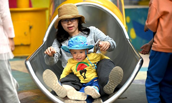 A mother and her baby playing on a slide at Wukesong shopping district in Beijing.