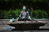 TOPSHOT - A woman wearing a face mask and goggles, amid concerns of the COVID-19 coronavirus, relaxes after exercising in a garden in Beijing on April 3, 2020. (Photo by WANG ZHAO / AFP)