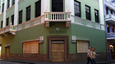 A couple in San Juan walk past a shop covered up with woodboard for protection before the anticipated arrival of Hurricane Maria.
