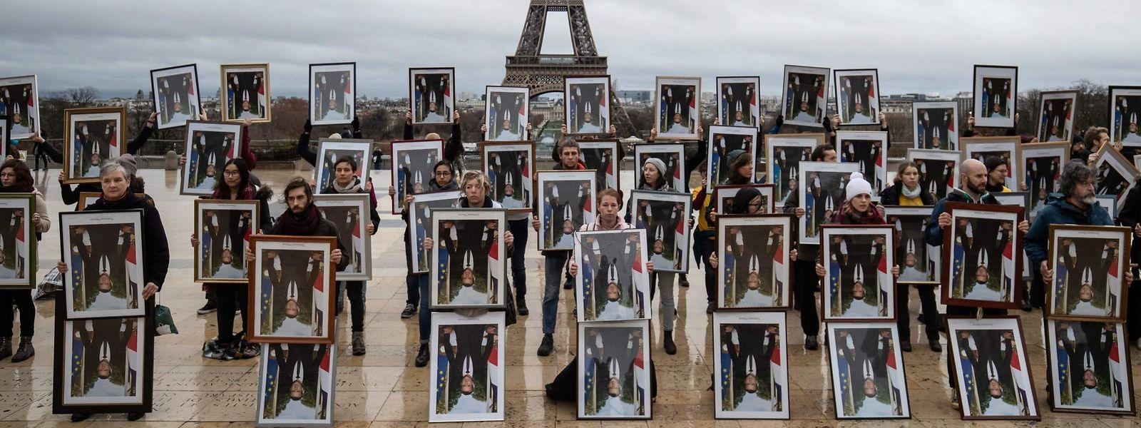 Französische Klimaaktivisten posieren mit 100 gestohlenen Macron-Porträts vor dem Eiffelturm.