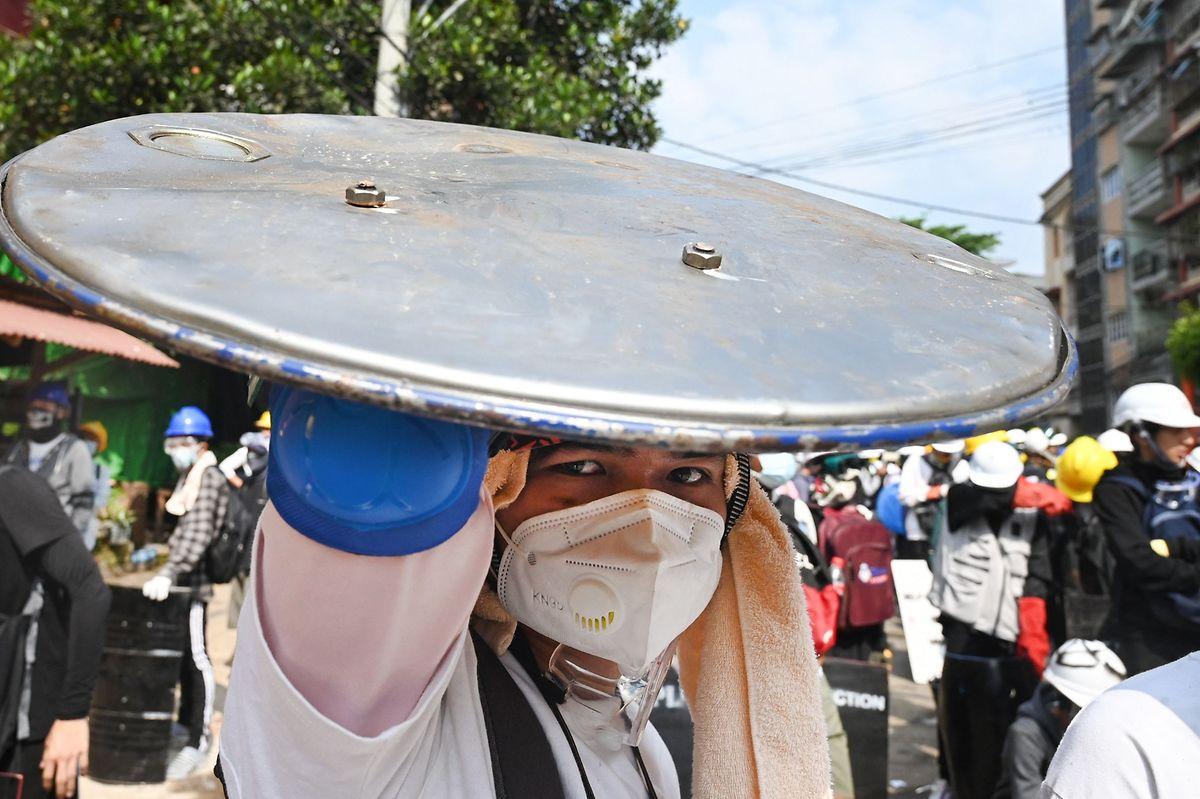 Ein Demonstrant hält einen selbst gebastelten Schild hoch, um sich vor Geschossen der Sicherheitskräfte zu schützen.