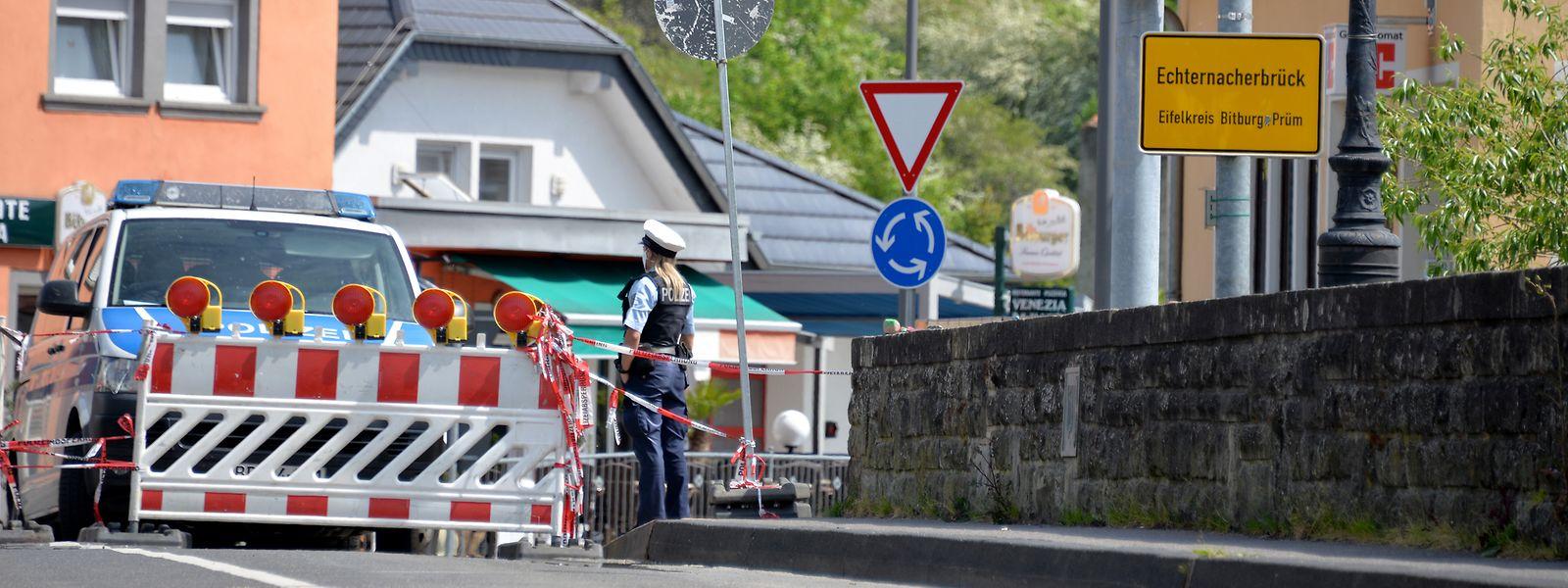 Eine Polizistin steht neben einer Straßensperre auf der deutschen Seite der Grenzbrücke die unerlaubte Einreise nach Luxemburg. In Echternach (Luxemburg) protestierten Vertreter des Echternacher Gemeinderats und des Eifelkreises Bitburg-Prüm gegen die Schließung der Grenze zwischen Luxemburg und Deutschland.