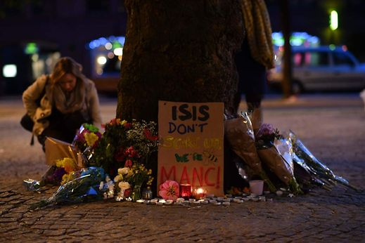 Messages and floral tributes are seen in Albert Square in Manchester