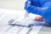 A coronavirus test is being processed at the fair grounds in Innsbruck, Austria, where a test centre has been installed as mass coronavirus testing started in the states of Vorarlberg and Tyrol as well as the capital Vienna on December 4, 2020. (Photo by Johann GRODER / various sources / AFP) / Austria OUT