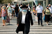 TOPSHOT - An ultra-Orthodox Jewish man wearing a protective mask and shield against the coronavirus,  walks along a street in Jerusalem on September 11, 2020. - Israel this week imposed new restrictions on parts of the country to confront a resurgence of Covid-19 infections, with the Arab-Israeli community especially hard hit in a second wave. (Photo by EMMANUEL DUNAND / AFP)