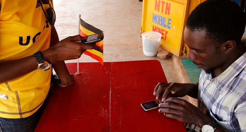 Ugandan woman sending money by cell phone. Uganda. (Photo by: Godong/Universal Images Group via Getty Images)