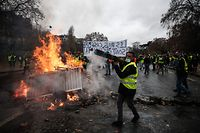 TOPSHOT - Protesters build a barricade during a protest of Yellow vests (Gilets jaunes) against rising oil prices and living costs, on December 1, 2018 in Paris. (Photo by Abdulmonam EASSA / AFP)