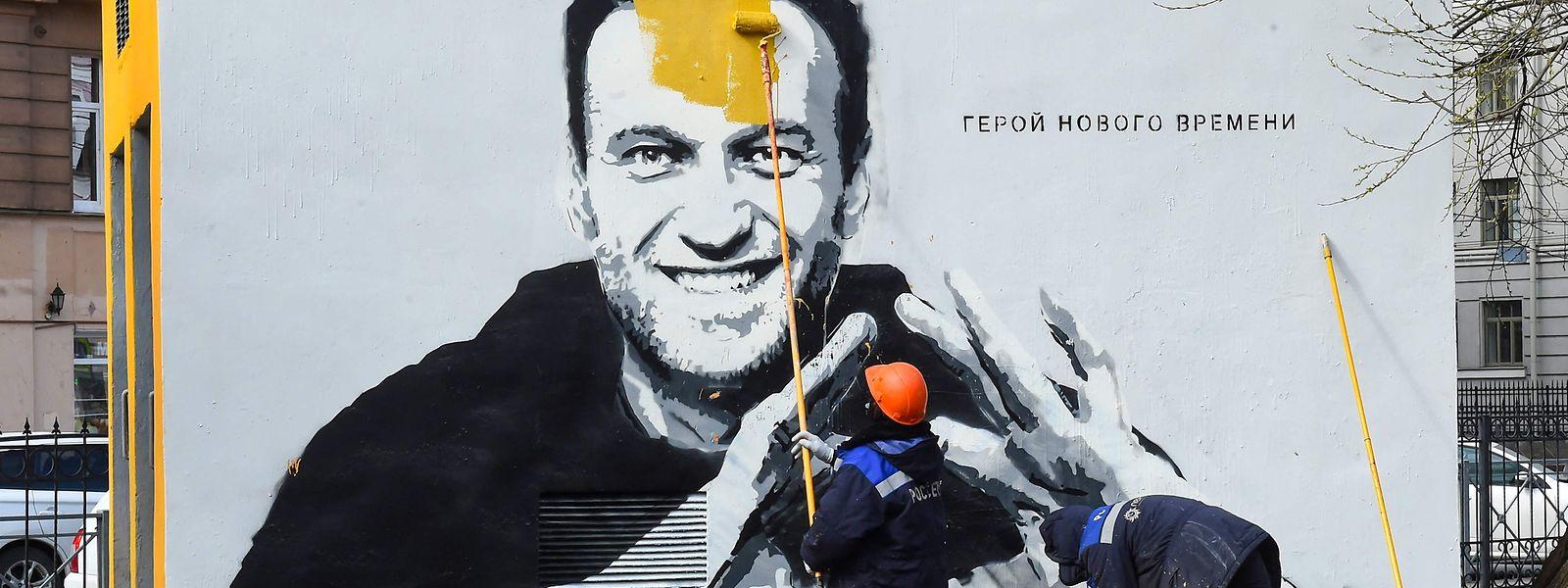 Ein Arbeiter übermalt ein Graffiti von Kremlkritiker Alexej Nawalny in Sankt Petersburg.