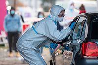 """27.10.2020, Hessen, Marburg: In einen Ganzkörper-Schutzanzug gekleidet ist ein Mitarbeiter eines Corona-Testzentrums auf dem Messegelände in Marburg. In einem """"Drive-In"""" werden Autofahrer hier direkt aus dem PKW heraus getestet. Foto: Boris Roessler/dpa +++ dpa-Bildfunk +++"""