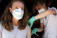 30.05.2021, Berlin: Eine junge Frau lässt sich in der Revolte-Bar im Berliner Bezirk Friedrichshain mit dem Impfstoff Johnson & Johnson impfen. Ein Kinderarzt und seine medizinischen Fachangestellten bieten, neben Corona-Schnelltests, in den Räumen, wo sonst Getränke ausgeschenkt werden, erstmals Impfungen an. Um eine Ausbreitung des Coronavirus weiter einzudämmen, wird in der ersten Bar Deutschlands am Wochenende das Serum des amerikanischen Herstellers Johnson & Johnson verabreicht. Bei diesem Impfoff bedarf es nur einer Impfung. Foto: Wolfgang Kumm/dpa +++ dpa-Bildfunk +++