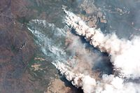 """This handout satellite image taken on December 31, 2019 and received from Planet Labs, Inc. on January 7, 2020 shows smoking rising into the air from bushfires near Lake Conjolia in the Australian state of New South Wales. - Firefighters raced to contain massive bushfires in southeastern Australia on January 7, taking advantage of a brief drop in temperatures and some much-needed rainfall before another heatwave strikes later this week. (Photo by Handout / 2019 Planet Labs, Inc. / AFP) / -----EDITORS NOTE --- RESTRICTED TO EDITORIAL USE - MANDATORY CREDIT """"AFP PHOTO / 2019 Planet Labs, Inc."""" - NO MARKETING - NO ADVERTISING CAMPAIGNS - DISTRIBUTED AS A SERVICE TO CLIENTS  - NO ARCHIVES"""