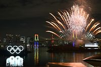 """(FILES) In this file photo taken on January 24, 2020 the Olympic rings (L) are displayed off the shore of the Odaiba Marine Park as fireworks explode during the Tokyo 2020 Year Commemorative Ceremony in Tokyo, to mark six months before the opening of the Tokyo 2020 Olympic Games. - Japan has asked for a one-year postponement of the Tokyo 2020 Games over the global coronavirus pandemic, and the International Olympic Committee has agreed, the country's prime minister said on March 24, 2020. """"I proposed to postpone for about a year and president Bach responded with 100 percent agreement,"""" Shinzo Abe told reporters referring to Thomas Bach, head of the IOC. (Photo by Kazuhiro NOGI / AFP)"""