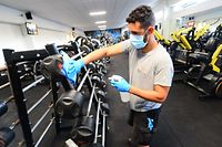 """(FILES) In this file photo taken on June 1, 2020 A worker disinfects barbells at the """"Body Staff Gym"""" fitness centre in Artigues-pres-Bordeaux, southwestern France, as part of safety measures on the eve of the reopening of the gym, as France eases lockdown measures taken to curb the spread of the COVID-19 pandemic, caused by the novel coronavirus. - Sports and fitness centers lost on September 30, 2020, in Bordeaux the first of the lawsuits they launched throughout France against their closure for two weeks in order to curb the spread of the coronavirus (Covid-19). (Photo by MEHDI FEDOUACH / AFP)"""