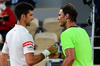Serbia's Novak Djokovic (L) and Spain's Rafael Nadal shake hands at the end of their men's singles semi-final tennis match on Day 13 of The Roland Garros 2021 French Open tennis tournament in Paris on June 11, 2021. (Photo by MARTIN BUREAU / AFP)