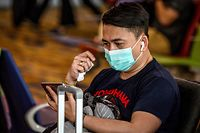 A passenger wears a face mask while waiting to board his flight at Yangon International Airport on January 21, 2020. - China has confirmed human-to-human transmission in the outbreak of a new SARS-like virus as the number of cases soared and authorities January 21 said a fourth person had died, as the World Health Organization said it would consider declaring an international public health emergency over the outbreak. (Photo by Mladen ANTONOV / AFP)