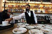 """02.03.2021, Spanien, Palma: Ali, Kellner in der """"Cristal-Bar"""", bereitet Kaffee zu. Nach einer siebenwöchigen Corona-Zwangsschließung haben die Gastwirte auf Mallorca erstmals wieder Gäste empfangen. Als Folge einer Verbesserung der Pandemie-Lage auf der Urlaubsinsel dürfen sie seit Dienstag die Außenbereiche wieder öffnen. Foto: Clara Margais/dpa +++ dpa-Bildfunk +++"""