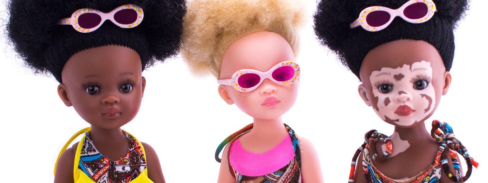 Drei Puppen aus der Sibahle Collection: eine Puppe mit Afrohaaren, eine Puppe mit Albinismus und eine Puppe mit Vitiligo.