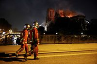 TOPSHOT - Firefighters look a fire at the landmark Notre-Dame Cathedral in central Paris as they cross the Archeveche Bridge on the Seine river on April 15, 2019. - A fire broke out at the landmark Notre-Dame Cathedral in central Paris, potentially involving renovation works being carried out at the site, the fire service said. (Photo by GEOFFROY VAN DER HASSELT / AFP)